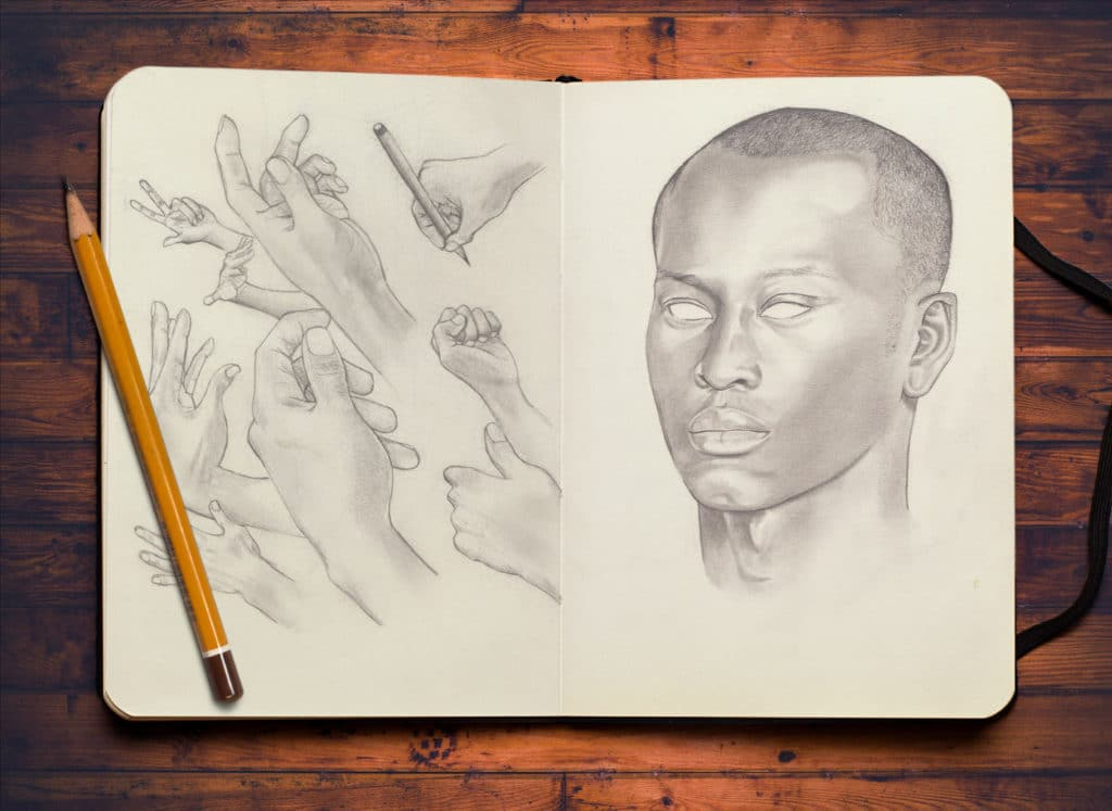 portait et plusieurs main dessinés sur un cahier de dessin avec un crayon posé à coté sur une table en bois